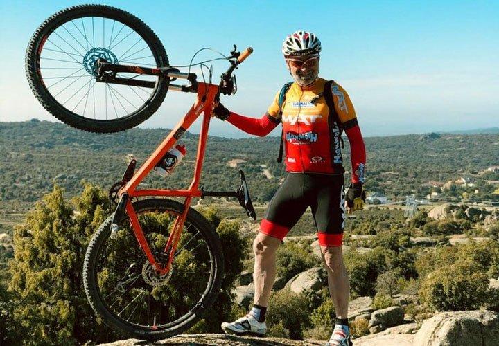 Tomás Martínez, trabajador de Grupo MAT y participante de la Titan Desert, sosteniendo una bicicleta